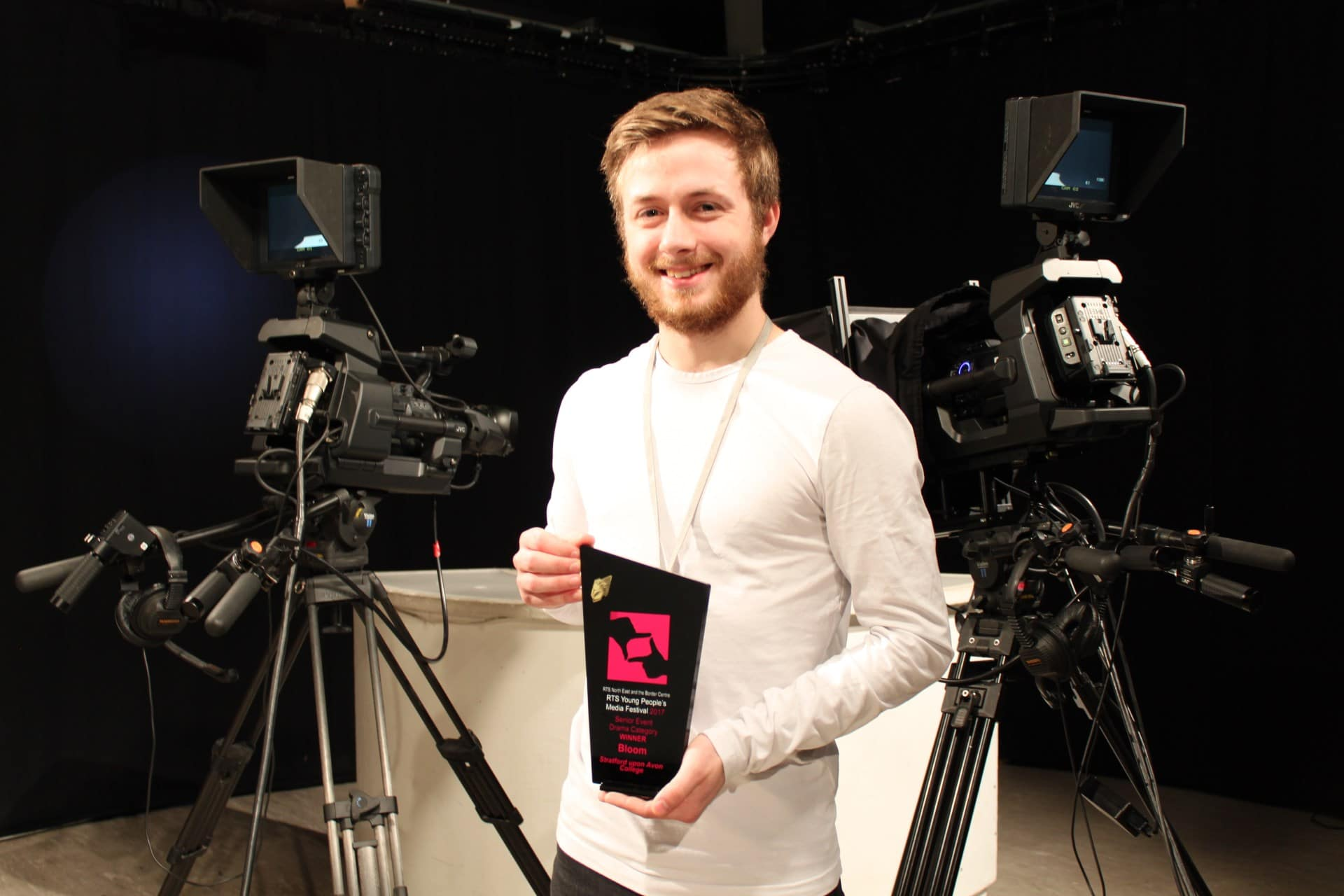 Alexander Eves proudly holding his award in Stratford-upon-College's television studio.