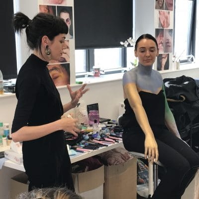 teacher explaining how to apply body paint
