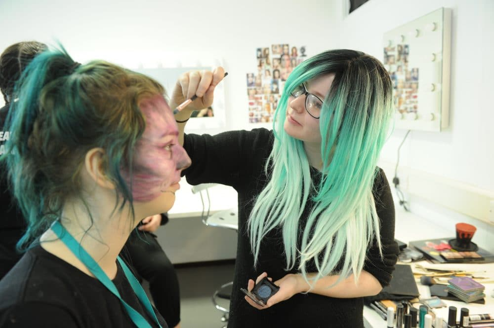 student putting make up on another student