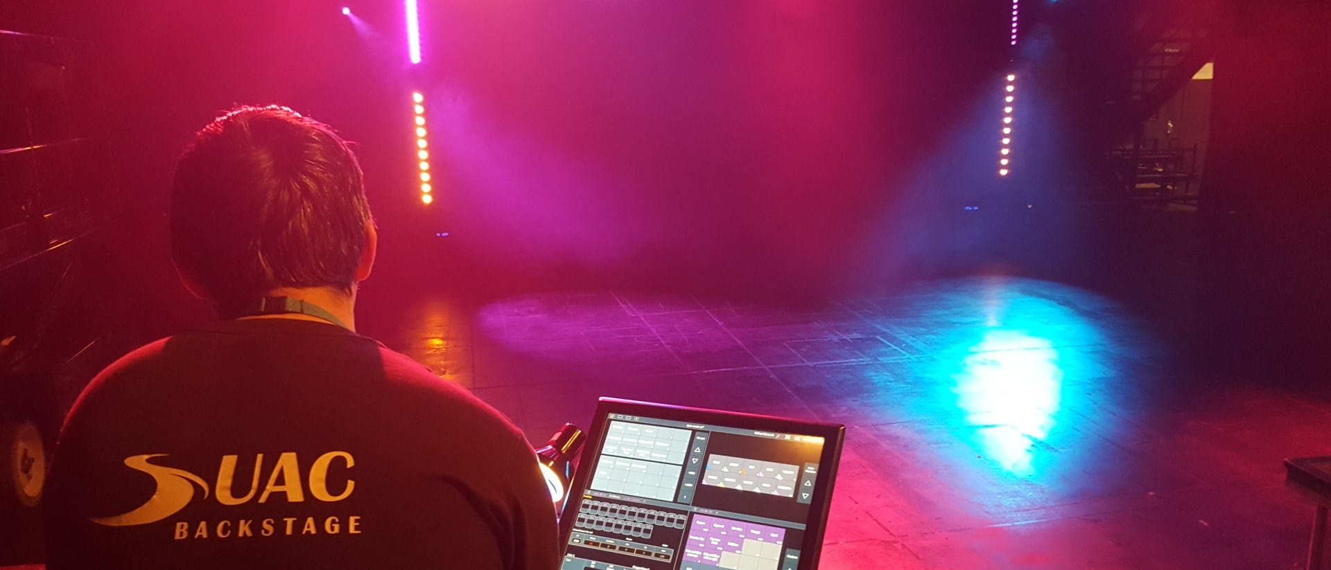 Student controls stage lighting using a computer.