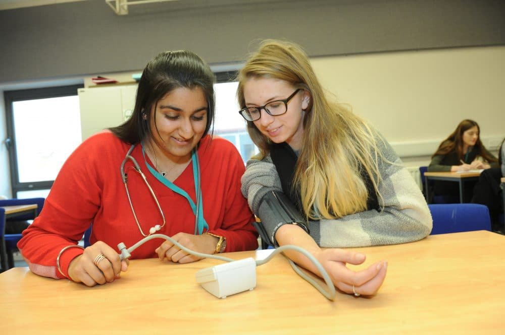 student taking blood pressure of other pupil