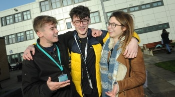Students embrace outside college building. School Leaver Advice Days.