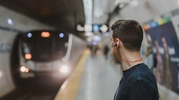 Man waiting for train at station. 'Author: Blur' 'Man Using Sports Earphones on Subway Train' https://www.pexels.com/photo/adult-blur-commuter-earphone-374621/