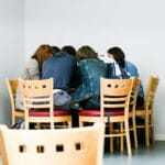 Students huddle around a table in a café.