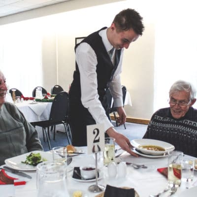Student serves at Friendship Lunch Club