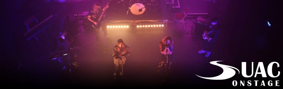 Two singers perform with a band